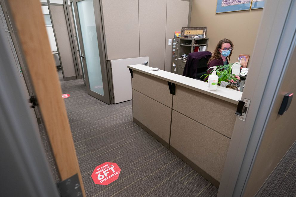 Emily Garrett works in an office with signs on the floor to remind employees to maintain appropriate social distancing at Alyeska Pipeline Service Company on Thursday, May 14, 2020 in Anchorage. (Loren Holmes / ADN)