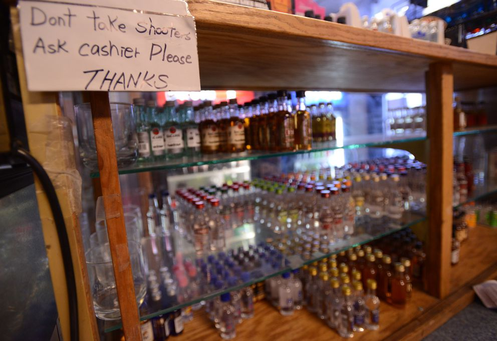 Small bottles of liquor, called shooters, are on shelves behind the cashier counter at Mom and Pop's Liquor Store, Jan. 3, 2018. (Anne Raup / ADN)