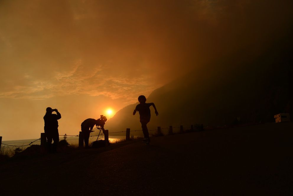 People stop at the Beluga rest stop along the Seward Highway and Turnagain Arm to look at the McHugh Creek Fire on the evening of Monday, July 18, 2016 south of Anchorage, AK. (Bob Hallinen / Alaska Dispatch News)
