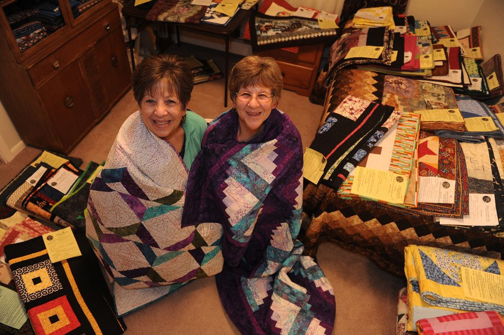 "Debby Hudson, is wrapped in her Quilt ""Path to Hawaii and Friends"" and her sister, Becky Rudisill is wrapped in her quilt ""Curvy Log Cabin"" Anchorage, AK on Wednesday, Nov. 7, 2018. The sisters are in the middle of planning the display of over 200 quilts for a silent auction. (Bob Hallinen / ADN)"