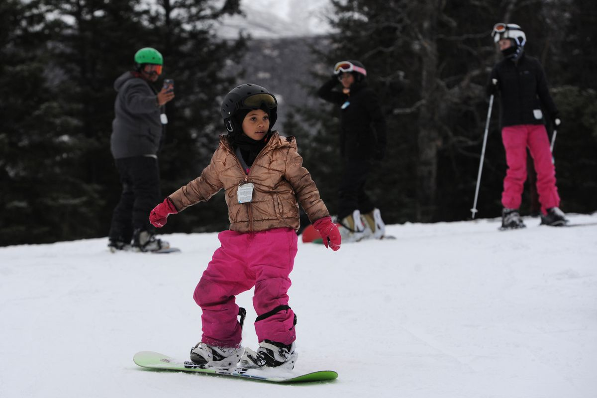 Gia Walker, 7, glides across artificial snow at Hilltop Ski Area while snowboarding on Sunday. (Bill Roth / ADN)