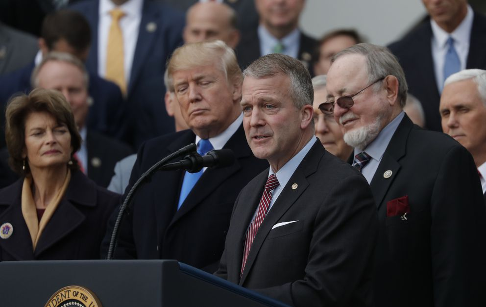 President Donald Trump stands with Alaska Republican Sen. Lisa Murkowski, Rep. Don Young and Sen. Dan Sullivan while celebrating with congressional Republicans after Congress passed sweeping tax overhaul legislation on the South Lawn of the White House in Washington on Wednesday. (Carlos Barria / Reuters)