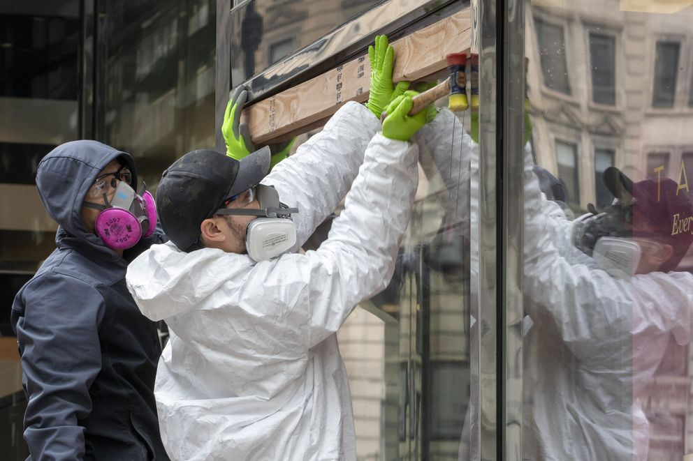 Carpenters wear protective gear as they board up the closed Sephora store on 34th St., Friday, March 20, 2020, in New York. (AP Photo/Mary Altaffer)