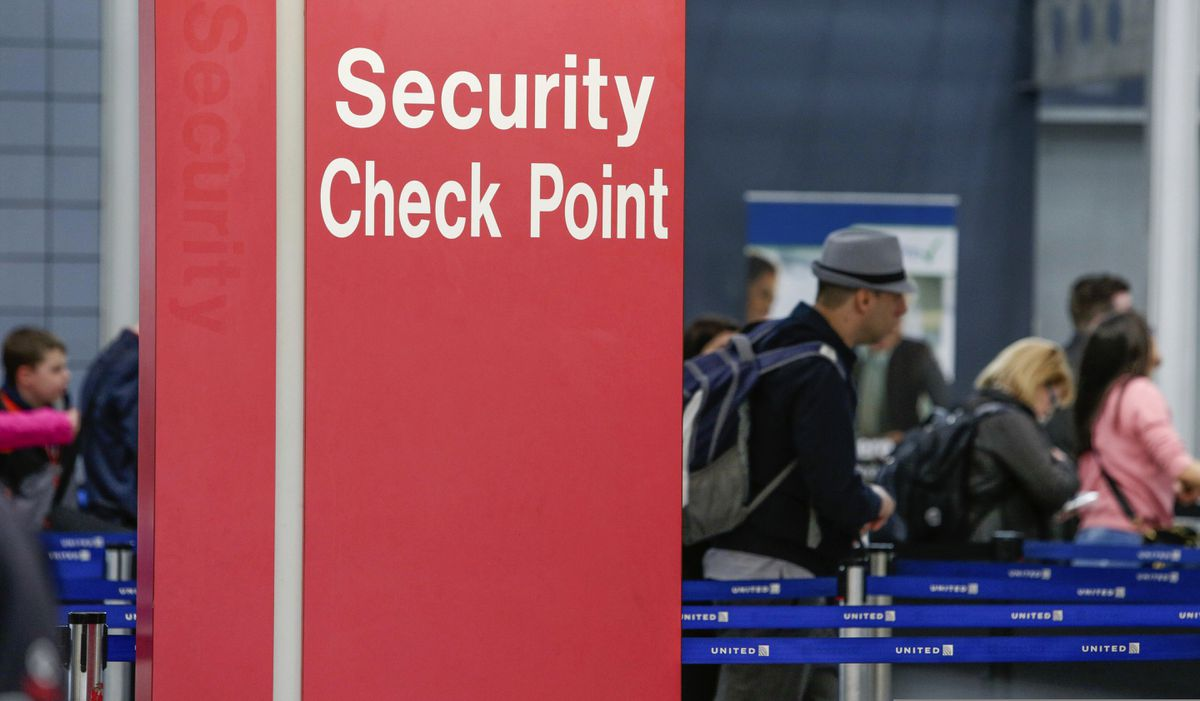 In this March 22, 2016 file photo, passengers check into their flights near a security checkpoint sign at O'Hare International Airport in Chicago. (AP Photo/Teresa Crawford, File)