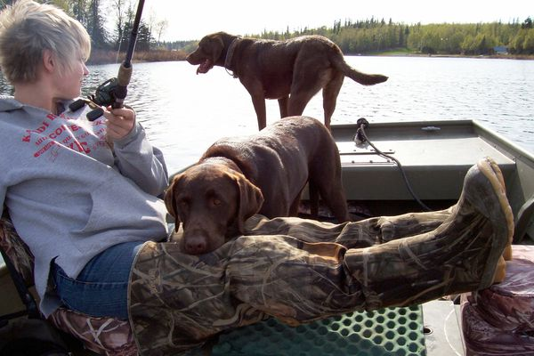 Christine Cunningham fishes with help from Jack and Gunner. (Photo by Steve Meyer)
