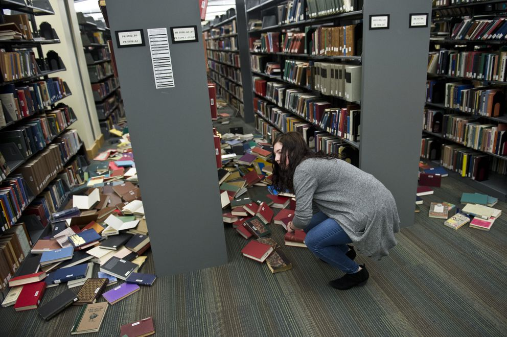 Systems librarian Margaret Hatty looks at toppled books inside the Consortium Library at UAA. An earthquake caused damage in the Anchorage area on November 30, 2018.