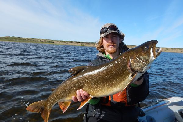 Kurt Heim shows a lake trout he caught in the Fish Creek watershed on the Arctic Coastal Plain. (Courtesy of Lydia Smith)