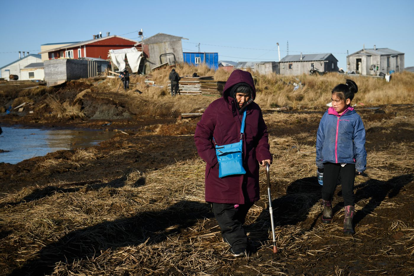 Teresa Charles, left, walks to a boat that would take her across the Ninglick River from Newtok to Mertarvik. (Marc Lester / ADN)