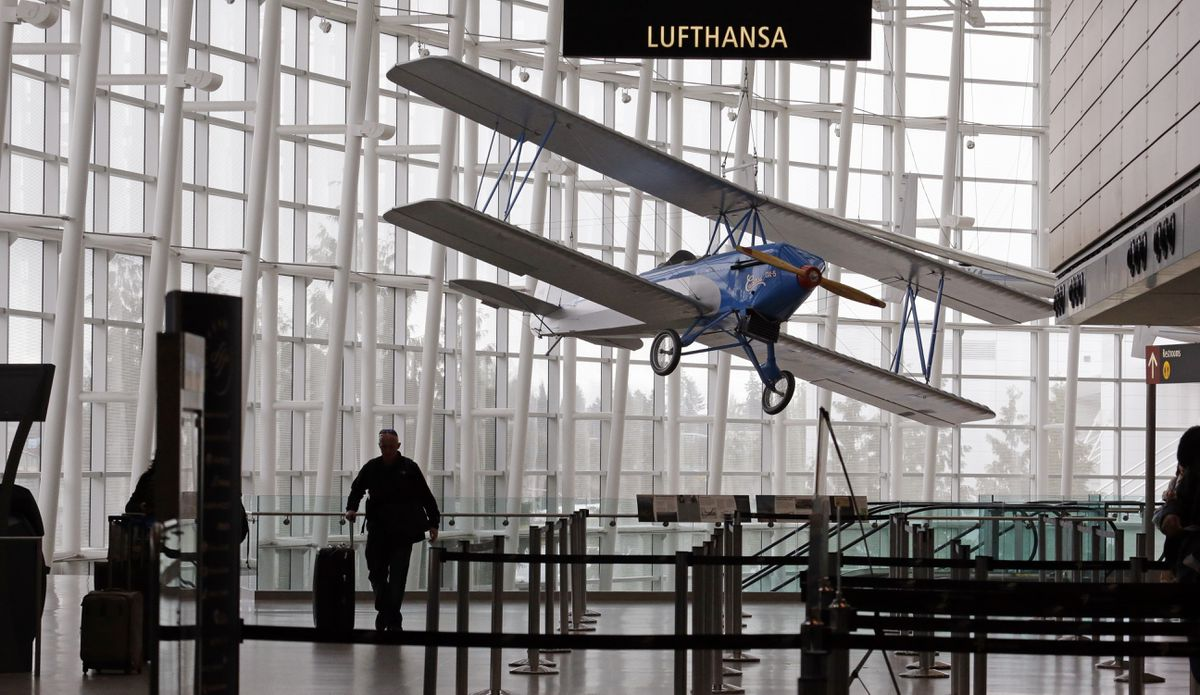 An airline traveler walks in view of a 1926 Alexander Eaglerock Combo-Wing airplane displayed at Seattle-Tacoma International Airport in 2015. (Elaine Thompson / AP file)