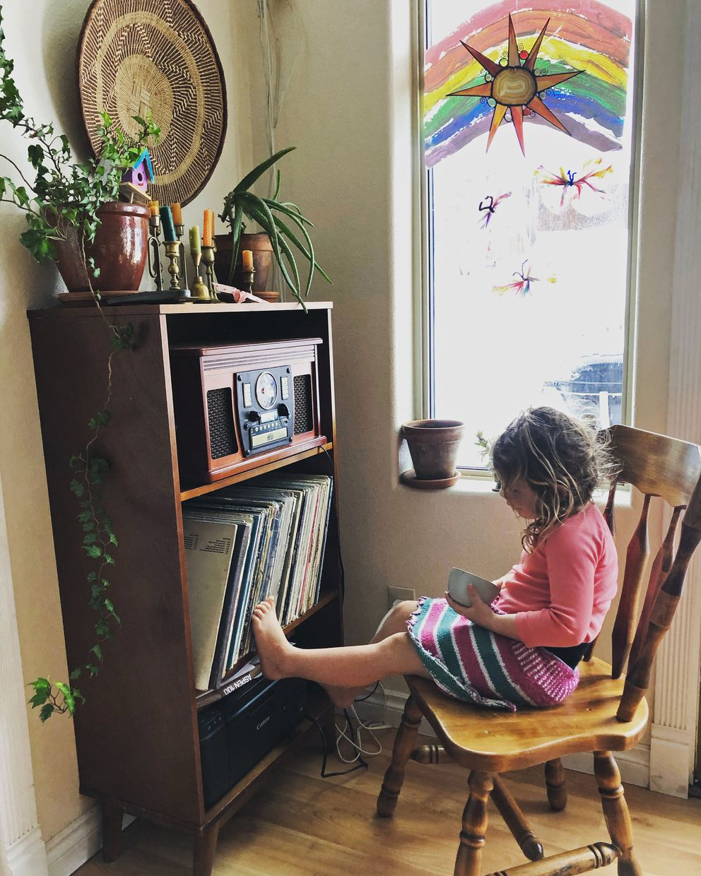 In this April 2, 2020, photo provided by Cassy Quinlan, 4-year-old Polly Fraley listens in Homer, Alaska, to children's stories being read on air at local radio station KBBI by librarian Claudia Haines. The library teamed up with the station to continue its popular story hour for preschoolers after it closed to the public amid coronavirus concerns. It's among ways the nation's libraries are dealing with closures amid coronavirus concerns. (Cassy Quinlan via AP)