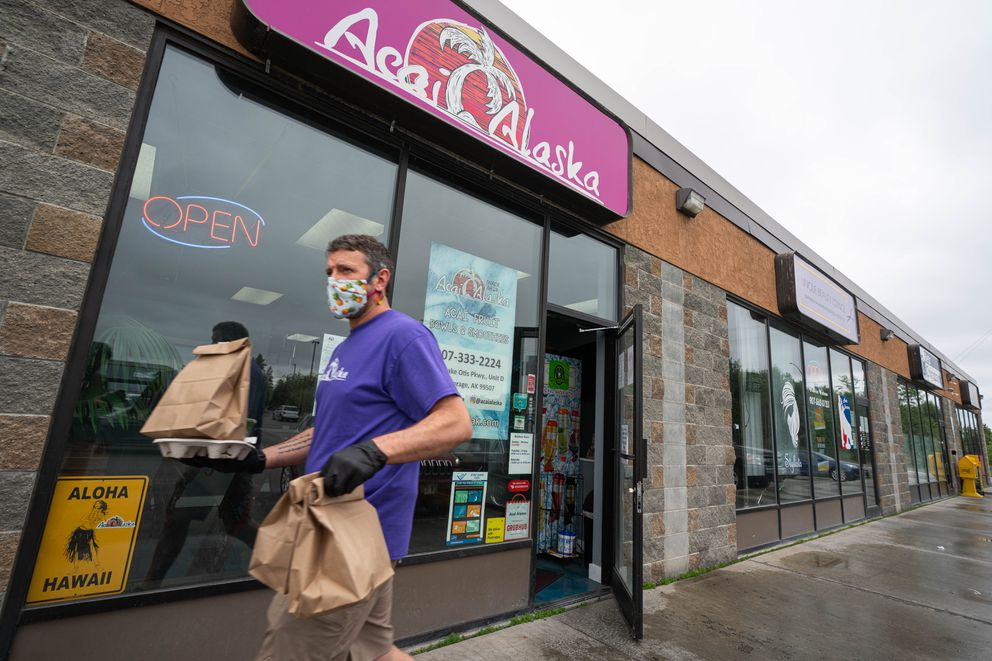 Acai Alaska owner Nathan Laabs delivers orders to drive-up customers at his business on Friday, June 19, 2020 in South Anchorage. (Loren Holmes / ADN)