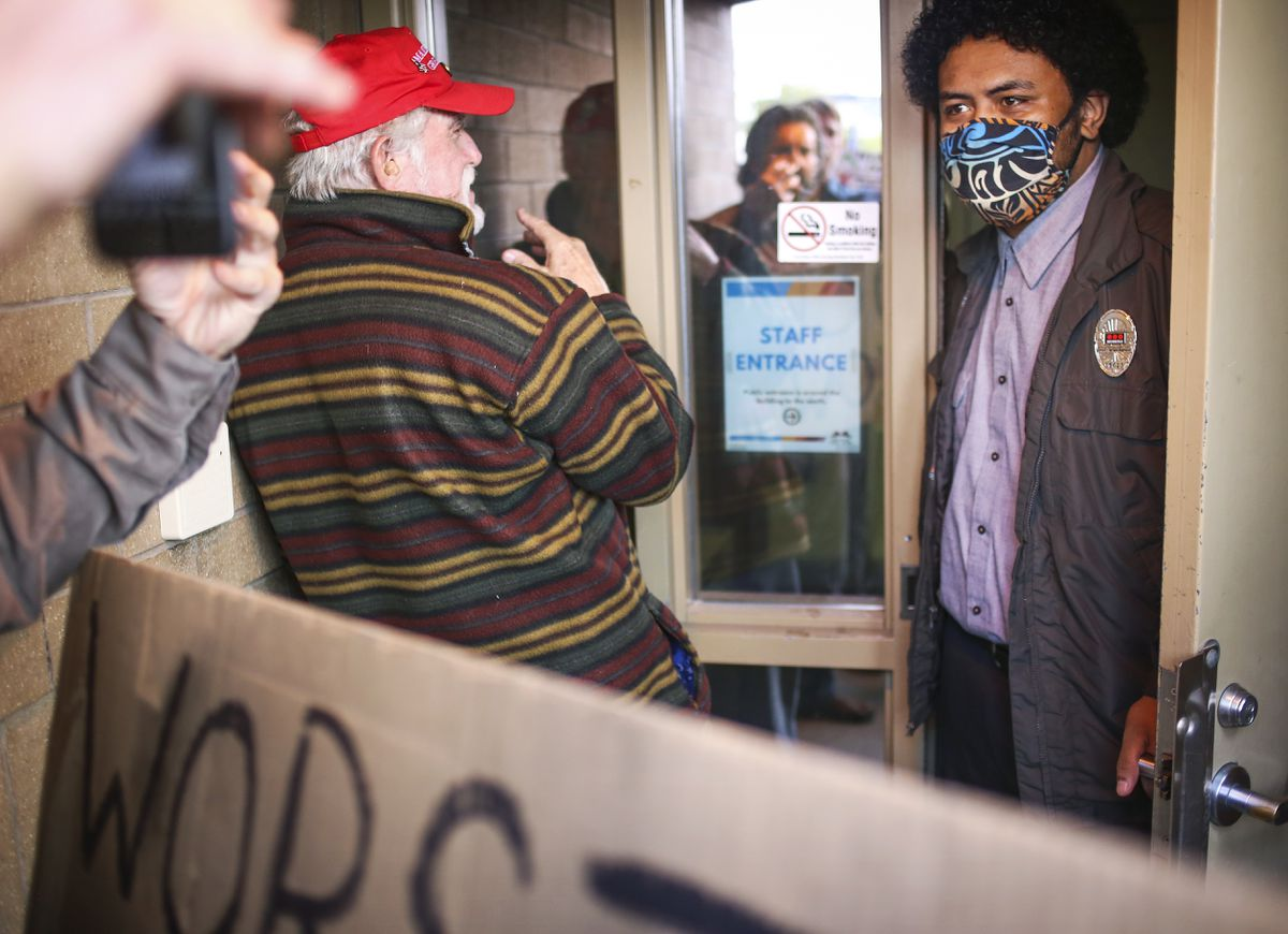 Marty Grossman, left, asks Tominic Latwer, a security guard at the Loussac Public Library, to let protesters into the building to attend the Anchorage Assembly meeting on Aug. 11, 2020. (Emily Mesner / ADN)