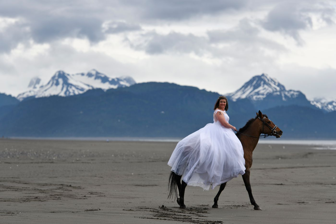 Lesley Zacharias wears her wedding dress and rides her horse, Maddy, on the beach along the Homer Spit on June 19, 2018. (Marc Lester / ADN)