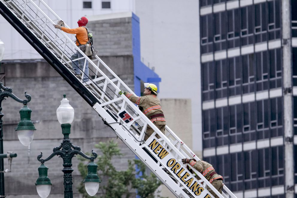 A rescued worker, left, and a firefighter look back at the damaged building after a large portion of a hotel under construction suddenly collapsed in New Orleans on Saturday, Oct. 12, 2019. (Scott Threlkeld/The Advocate via AP)