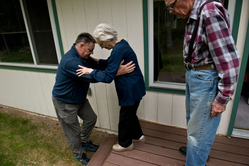 Doug Haralson helps his mother walk down steps in her backyard on June 7, 2017. Don Haralson is at right.  (Marc Lester / Alaska Dispatch News)