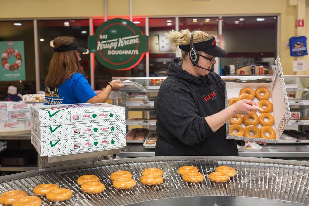 Amber Starks packages a dozen doughnuts at Krispy Kreme on Wednesday, Dec. 14, 2016. (Loren Holmes / Alaska Dispatch News)