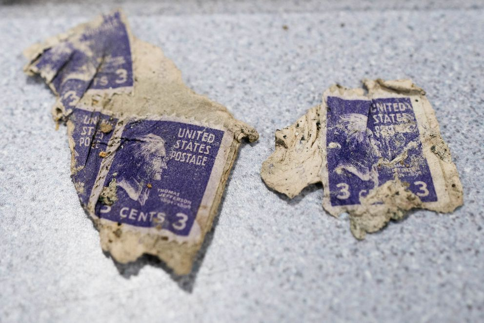 3-cent postage stamps featuring a likeness of Thomas Jefferson, recovered from Colony Glacier, are displayed at a press conference Friday, June 26, 2020 at Joint Base Elmendorf-Richardson. Operation Colony Glacier 2020, which is a recovery effort for human remains and artifacts from the 1952 crash of a C-124 Globemaster cargo plane, wrapped up on June 23. (Loren Holmes / ADN)