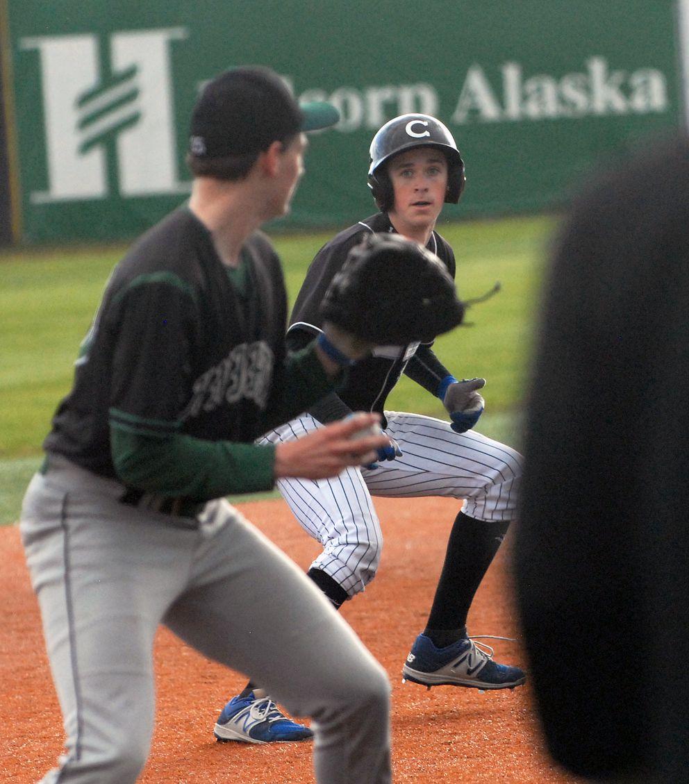 Chugiak's Garrett Nevells watches as Colony third baseman Ben Alleyprepares tothrow to first base duringThursday's late game. (Matt Tunseth/Alaska Star)