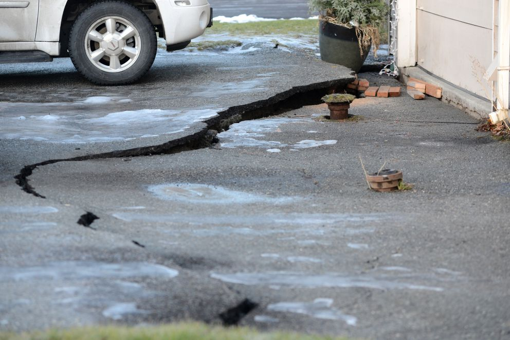 A corner of Nikki and Mike Rose's home dropped during the Nov. 30, 2018, earthquake, causing the driveway pavement to crack. The water shutoff, or keybox, remained at its original height. Photographed Dec. 3, 2018. (Anne Raup / ADN)