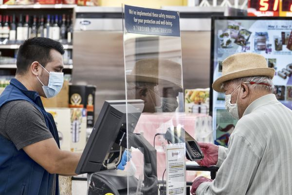 A grocery worker, wearing a protective mask and gloves, helps checking out a customer from behind a plexiglass barrier at the 99 Ranch Market in the Van Nuys section of Los Angeles on Tuesday May, 5, 2020. (AP Photo/Richard Vogel)