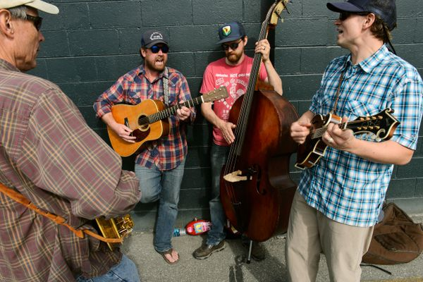 Four musicians gathered on a sidewalk in Midtown Anchorage to play Friday afternoon, August 31, 2018 The group said they gather on Benson Boulevard near Spenard Road each Friday from 11 a.m. to 1 p.m. to jam. From left, Jim Smith plays banjo, Todd Grebe plays guitar, Danny Booth plays the upright bass and Jason Norris plays mandolin. Check out their bluegrass sound in this video. (Marc Lester / ADN)