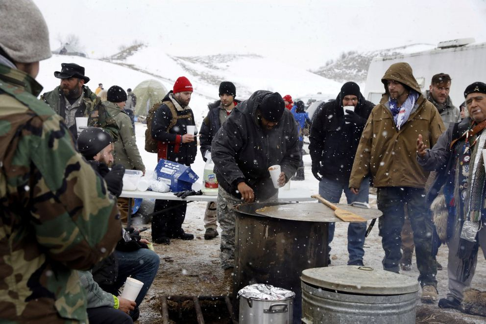 """Veterans eat from a communal kitchen inside of the Oceti Sakowin camp during a snowfall as """"water protectors"""" continue to demonstrate against plans to pass the Dakota Access pipeline adjacent to the Standing Rock Indian Reservation, near Cannon Ball, North Dakota, December 5, 2016. REUTERS/Lucas Jackson"""
