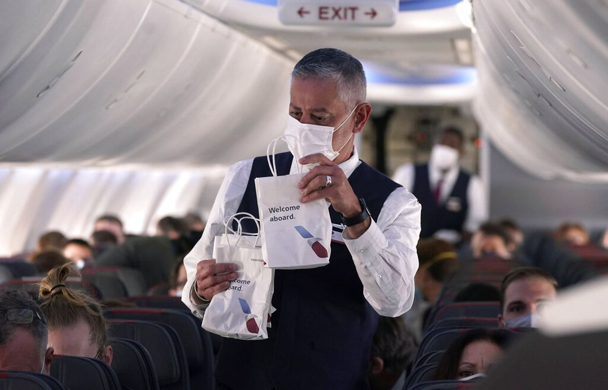 An American Airlines flight attendant hands out snack bags. (AP Photo/LM Otero)