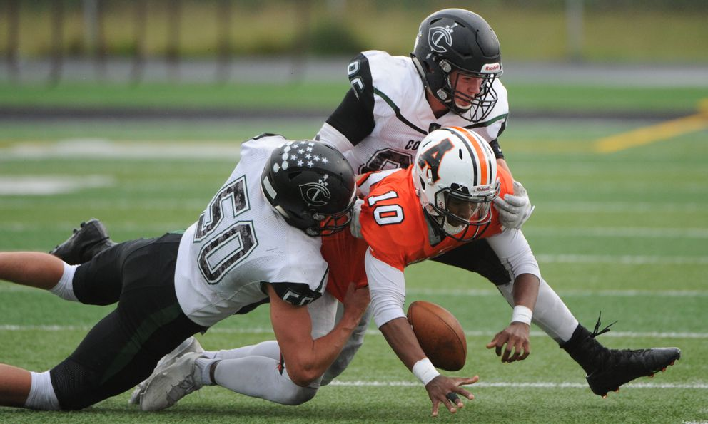 West High quarterback Qyntyn Pilcher is sacked by Colony defenders Jarrett Villastrigo (50) and Jarek Schultz (86) during the Knights' 46-15 victory over the Eagles on Thursday. (Bill Roth / Alaska Dispatch News)