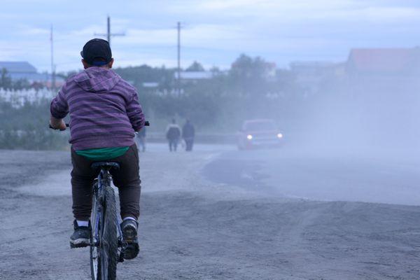 A cyclist travels along Ridgecrest Drive in Bethel, Alaska, on Aug. 4, 2017 -- a warm and dusty day. (Lisa Demer / Alaska Dispatch News)