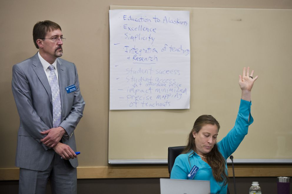 Regent Cachet Garrett, right, raises her hand to make comments as Myron Dosch, chief finance officer for University of Alaska, makes notes on paper during the discussion. (Marc Lester / ADN)