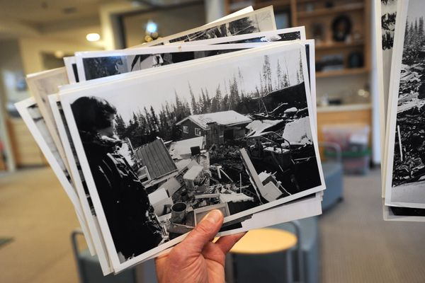 Anne Thomas Donaghy holds a photograph of her mother Tay Thomas and their Turnagain Heights home that was damaged that was damaged during the 1964 Earthquake while sharing her experiences with residents at the Thomas Center on Dec. 5. 2018. (Bill Roth / ADN)
