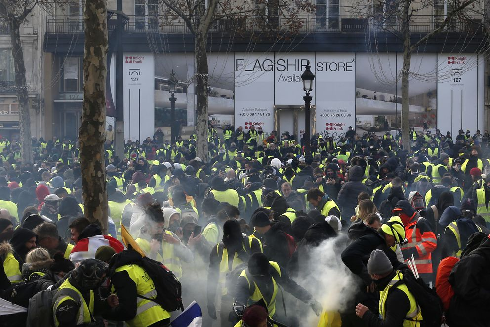 Demonstrators wearing yellow vests gather on the Champs-Elysees avenue Saturday, Dec. 8, 2018 in Paris. Crowds of yellow-vested protesters angry at President Emmanuel Macron and France's high taxes tried to converge on the presidential palace Saturday, some scuffling with police firing tear gas, amid exceptional security measures aimed at preventing a repeat of last week's rioting. (AP Photo/Rafael Yaghobzadeh)