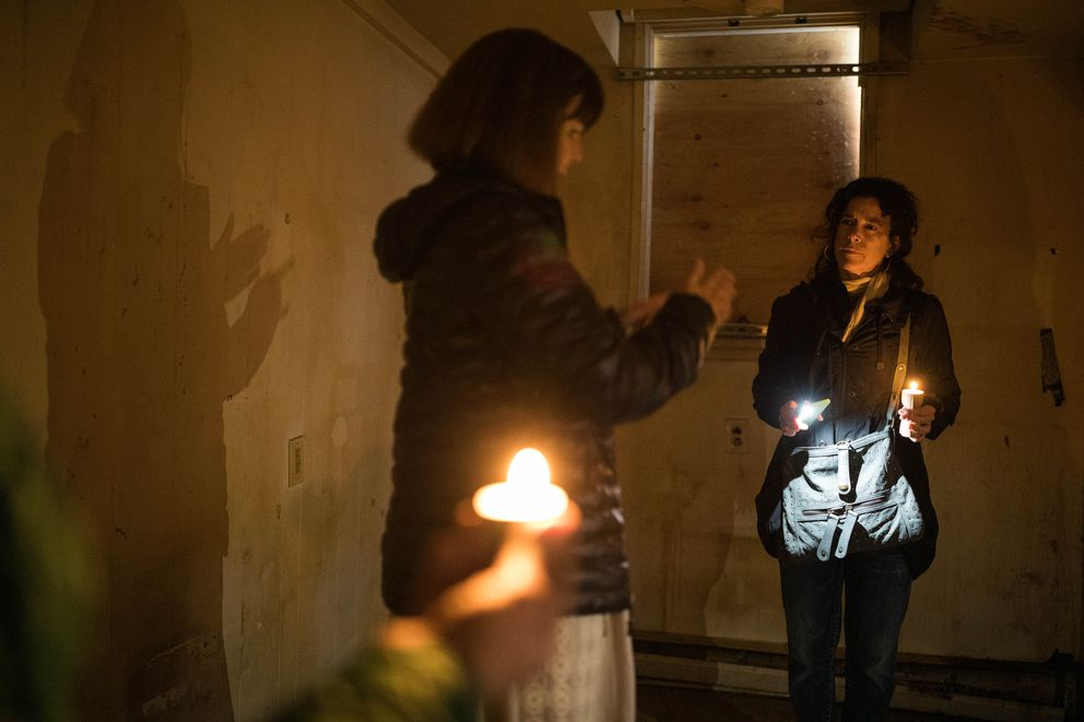 Cindy Berger, right, listens as medium Polly Wirum guides a group through the former Paradise Inn on May 17 to 'clear stagnant energy and bring in free-flowing energy. ' (Loren Holmes / ADN)