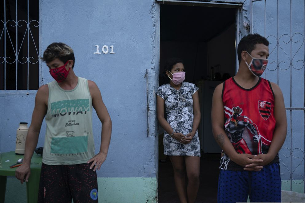 Caregiver Leandro Beiton, left, and relatives of the late Edgar Silva, wearing face masks amid the new coronavirus pandemic, stand by after his body was removed by SOS Funeral service workers in Manaus, Brazil, Tuesday, May 12, 2020. According to his family, Silva had Alzheimer's and died at home after two days of fever and difficulty breathing. (AP Photo/Felipe Dana)