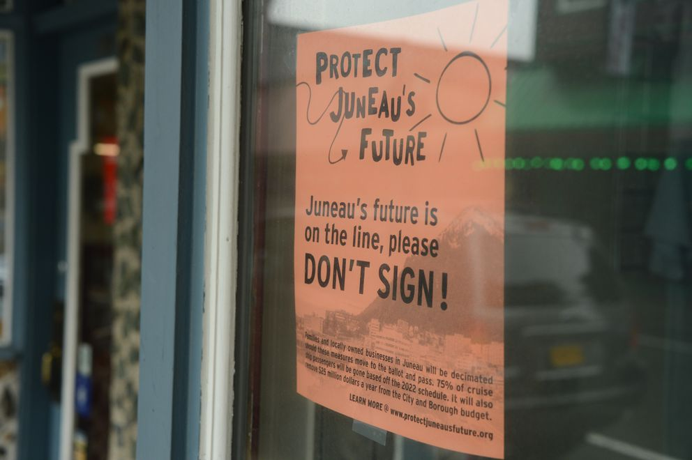 A flyer hanging in the window of the Alaska Fudge Company on Wednesday, June 2, 2021 urges city residents to not sign three petitions that would impose restrictions on local cruise ship traffic. (James Brooks / ADN)