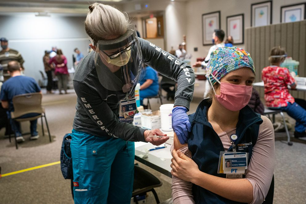 Registered Nurse Banu Mufale administers a Pfizer-BioNtech COVID-19 vaccine to physical therapist Becca Mamrol on Wednesday, Dec. 16, 2020 at Providence Alaska Medical Center in Anchorage. (Loren Holmes / ADN)