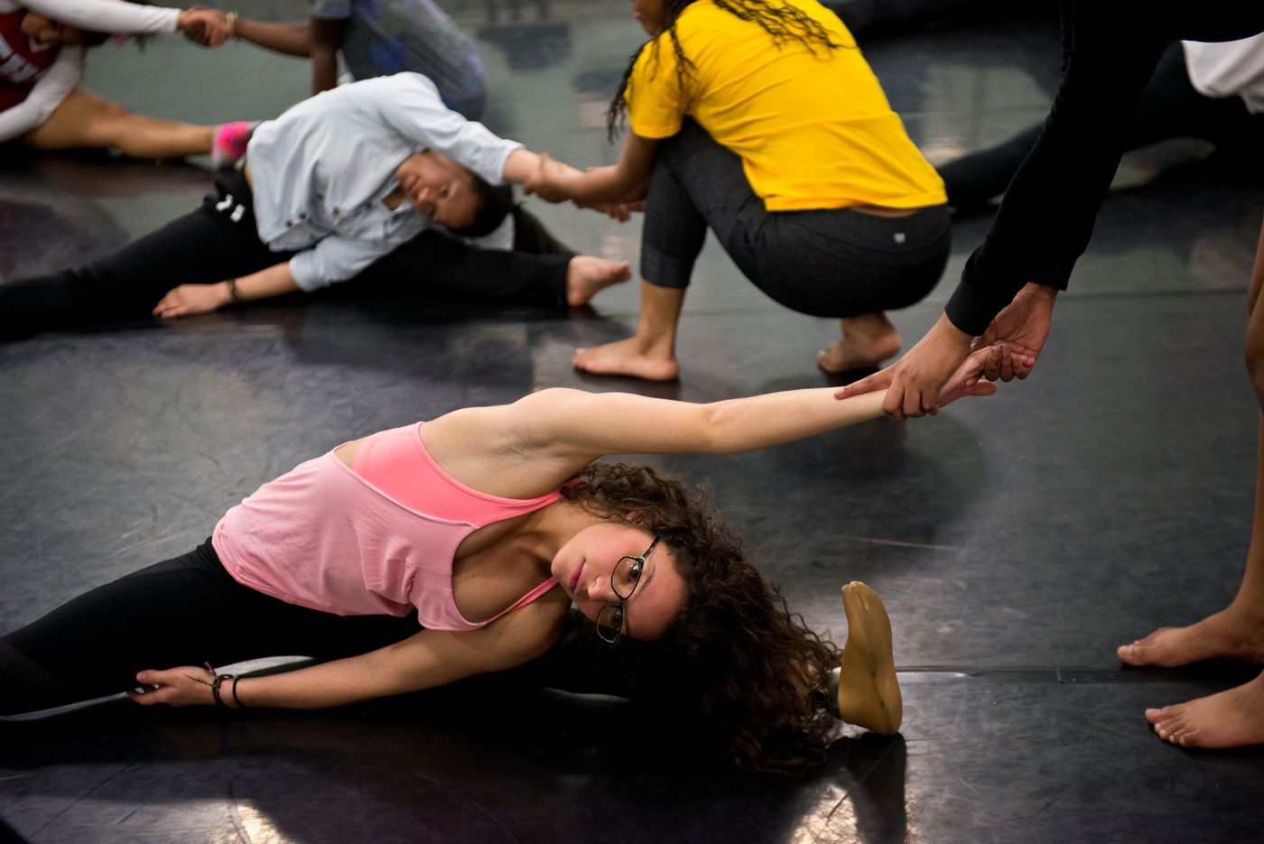 Taylor Haines stretches with others in East High School's Dance Contempo at the start of a rehearsal on Thursday, October 15, 2015.
