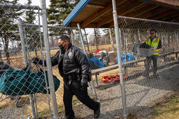 Anchorage Police Department officer Jesus Rivera helps Parks and Recreation employee AJ Correra remove belongings from a dugout at Davis Park on Wednesday, May 5, 2021 in Anchorage. A woman had been forced to move from her camp in a nearby forested area after a recent zone abatement, and spent a few nights in the dugout before being told to move again. Officer Rivera is part of APD's Community Action Policing team, which enforces illegal campsite abatement, coordinates cleanup with the Parks and Recreation department, and connects people experiencing homelessness with community resources. (Loren Holmes / ADN)