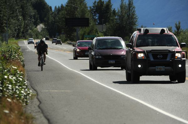 A biker rides on the shoulder of the Seward Highway next to Potter Marsh as traffic passes by on Thursday, August 9, 2018. (Bob Hallinen / ADN)