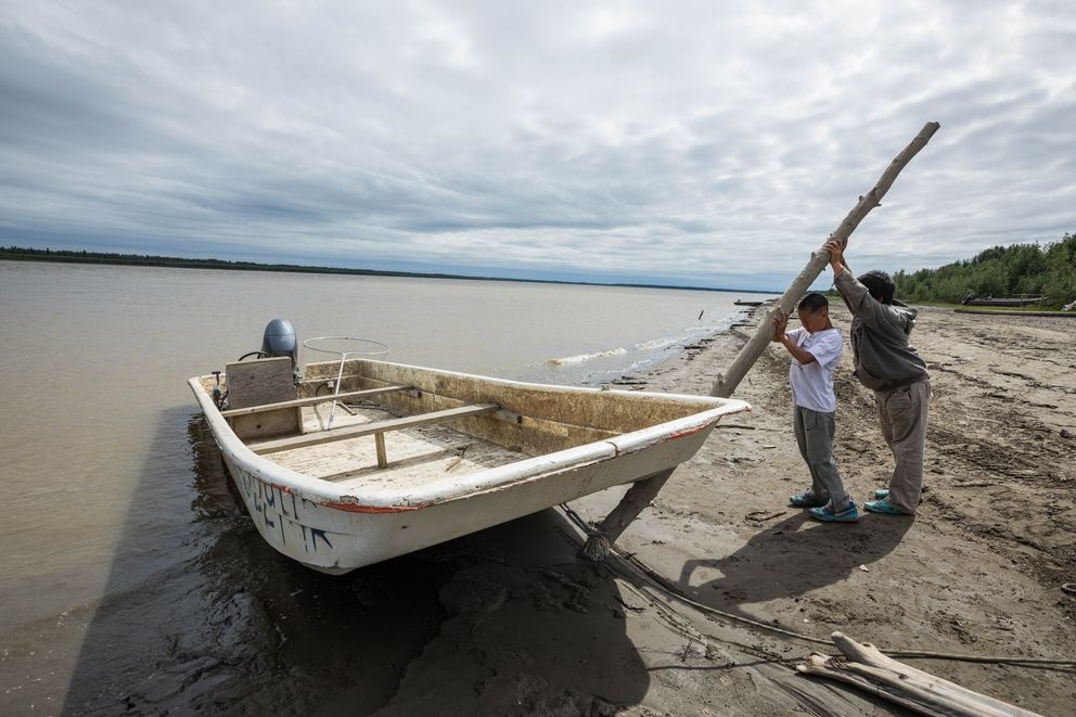 Jonathan Chunak, left, and Emmanuel Andrews try to push a boat into the water so they can go fishing. (Loren Holmes / ADN)