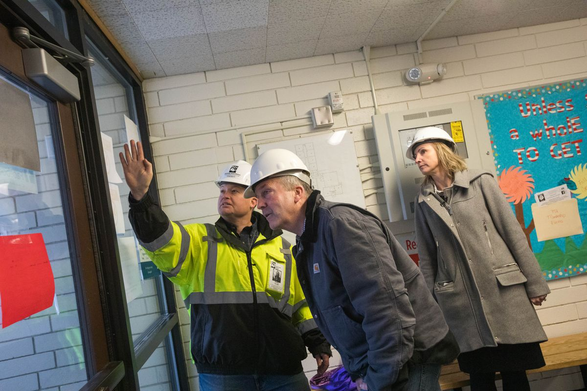 ASD's Thomas Fenoseff, Sen. Dan Sullivan and ASD superintendent Deena Bishop look at damage to the wall of the gym at Eagle River Elementary School on Dec. 4, days after a magnitude 7.0 earthquake damaged structures across Southcentral Alaska. (Loren Holmes / ADN archive)