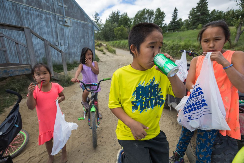 From left, Monica Kozevnikoff, 6, Syra Kozevnikoff, 9, Xavier Joseph, 10, and Charissa Kozevnikoff, 12, eat snacks outside the Russian Mission Native Store. (Loren Holmes / ADN)