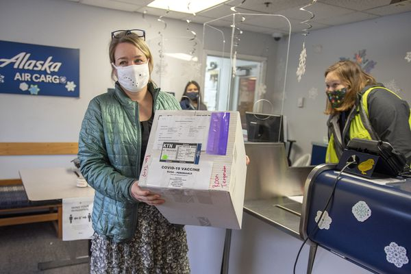 Public Health Nurse 4 Theresa Ruzek collects a shipment of 20 doses of the COVID-19 vaccine from Alaska Air Cargo Station Manager Madison Swafford on Wednesday, Dec. 16, 2020 at Ketchikan International Airport in Ketchikan, Alaska. (Dustin Safranek/Ketchikan Daily News via AP)