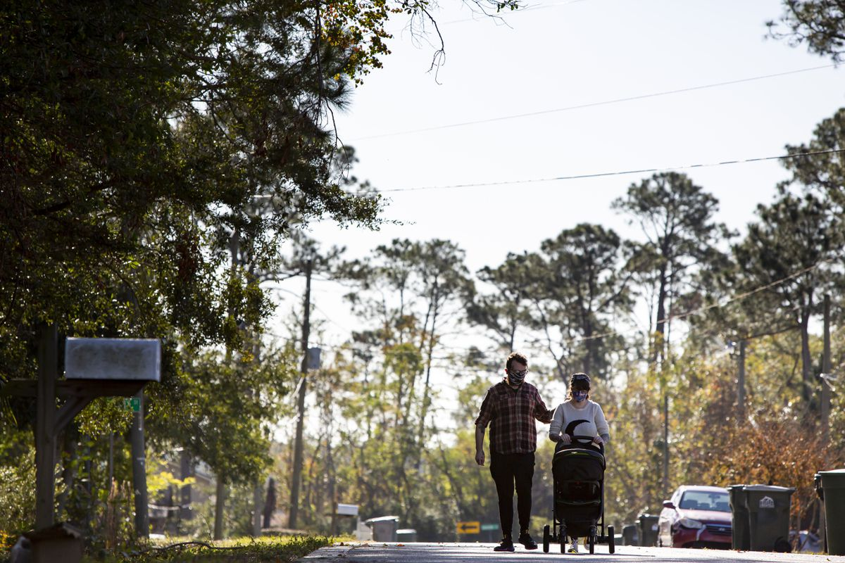 Katy Dobson and Aaron Walker take a walk with their son, Atlas, near their home in Pensacola, Fla., on Dec. 23. Atlas was conceived in the early days of the coronavirus pandemic and was born Dec. 8. MUST CREDIT: Photo by Meggan Haller for The Washington Post.