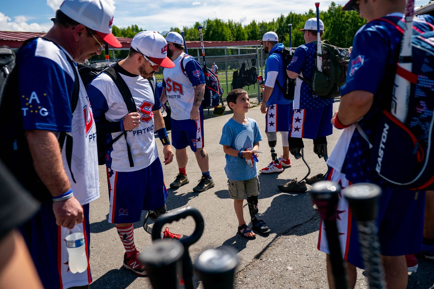 Six-year-old Justus Bohart of Seward, whose foot was amputated when he was 11 months old, talks with Patriots players Saturday at Cartee Fields 'He's just been dying to meet other amputees, ' said his mom, Rhonda Bohart. (Loren Holmes / ADN)