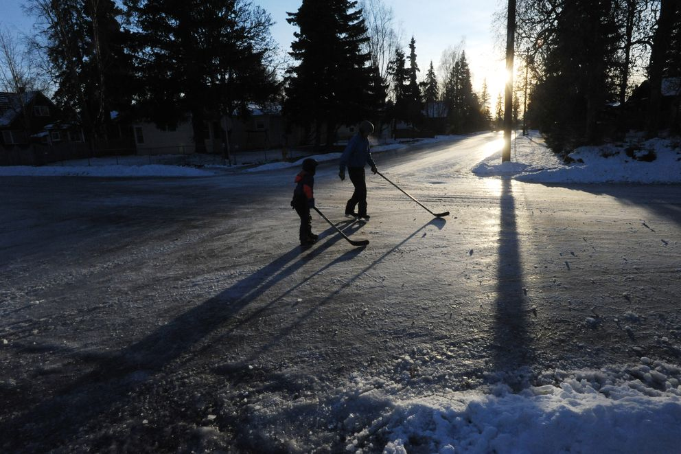 Jason Geck and his son Tucker Geck, 6, ice skate on the street on their way home after playing hockey on the icy roads near downtown Anchorage on Sunday, Dec. 8, 2019. (Bill Roth / ADN)