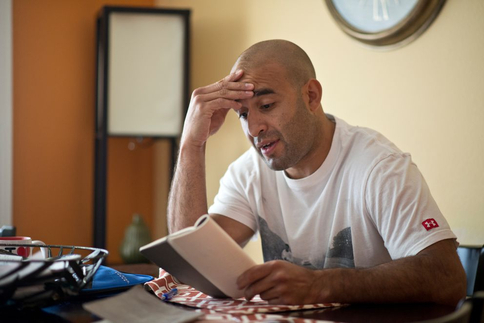 Scott Gomez reads a poem he wrote from one of his journals on Tuesday. Gomez said he often wrote while traveling as a hockey player. (Marc Lester / Alaska Dispatch News)