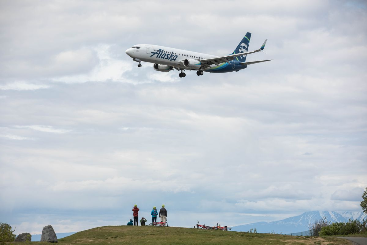 An Alaska Airlines 737 pilot waves at the Hutchins family as the plane lands Tuesday, May 29, 2018 at Ted Stevens Anchorage International Airport. (Loren Holmes / ADN)