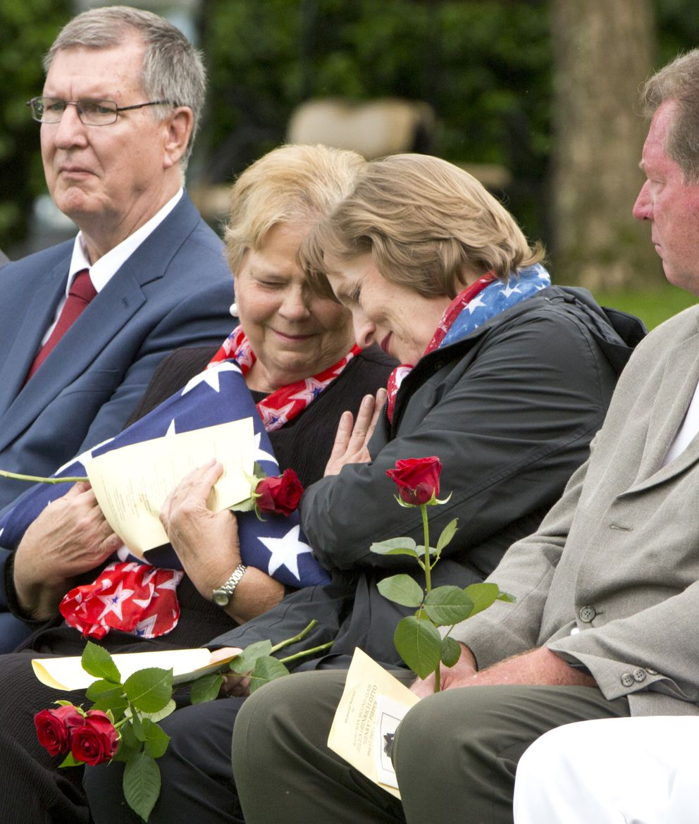 Family members of WWII U.S. Navy sailor Julius Pieper, Linda Suiter, second left, and Susan Lawrence, second right, during a reburial service for their uncle at the Normandy American Cemetery, Colleville-sur-Mer, France, Tuesday, June 19, 2018. Seventy four years to the day after their ship hit a mine off the coast of Normandy and sunk, Julius Pieper was finally reunited with his twin brother Ludwig. (AP Photo/Virginia Mayo)