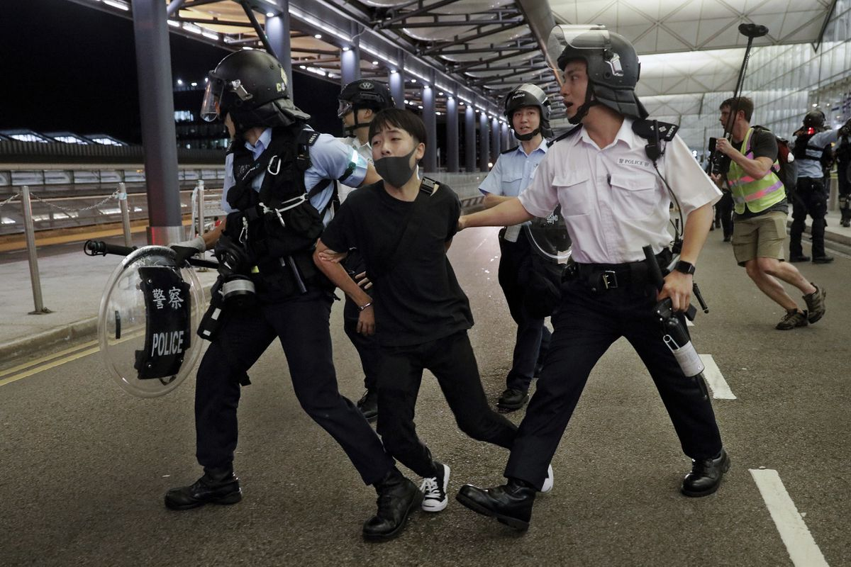 Policemen arrest a protester during a clash at the Airport in Hong Kong, Tuesday, Aug. 13, 2019. Riot police clashed with pro-democracy protesters at Hong Kong's airport late Tuesday night, a chaotic end to a second day of demonstrations that caused mass flight cancellations at the Chinese city's busy transport hub. (AP Photo/Vincent Yu)
